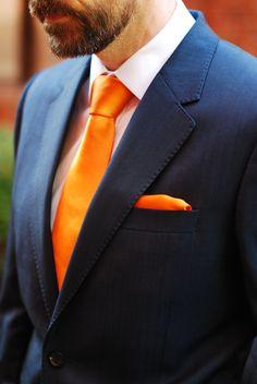 Good looking orange tie with navy suit.