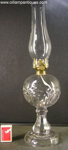 In the early part of the kerosene lighting era, the raised or sunken circle called a bullseye was a popular design for oil lamps and other glassware. The pattern of this antique glass oil lamp is called Panelled Bullseye. The weight and clarity of the glass used for this oil lamp indicate that it is leaded glass so it was made in the early 1860s. During the American Civil War (1861 – 1865), the use of lead in glass was outlawed because the lead was needed for military purposes.