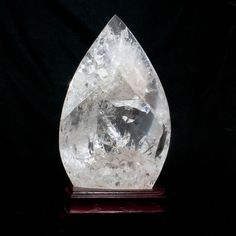 """Clear Quartz Flame will amplify any other stones energy that is around it, such as a protection stone, Clear Quartz Flame will strengthen the protection abilities as well as it being a protector itself. This stone is a cleanser of the mind, body and soul, also of any area it is kept in, by drawing away negative energies. This beautiful Quartz Flame comes with a stand. 12.5"""" x 7"""""""