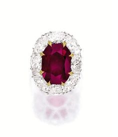 Lot 1813 – RARE RUBY AND DIAMOND RING  Centring on a cushion-shaped ruby weighing 12.28 carats, surrounded by eight oval diamonds together w...