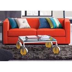 Hi-concept table rolls low profile on oversized aluminum wheels with new spin in bright fun pop of yellow enamel. Iron frame with silver powdercoat squares off clear glass top as sculpture.