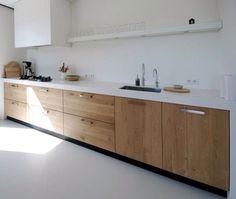Dans la cuisine, des éléments bas en bois et des éléments hauts blancs, sur mesure, prof 35 cm et qui vont jusqu'au plafond.