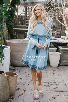 This soft, light blue chambray is the perfect addition to your spring wardrobe! The Juniper features cute bells sleeves, a smocked waist with a tie tassel, and pretty embroidery details.