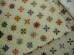 This is cool - one a day!  The finished quilts are approximately 80 inches square and are made from 364, three inch Le Moyne star blocks (i.e. tiny stars) and plain fabric squares. One-star-everyday of the year with the exception of your birthday and Christmas day. they were not permitted to repeat a fabric, therefore, they have 728 different fabrics in each quilt.  Jo wishes she would have been part of this great sew along!