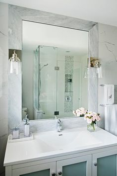 Frosted glass doors with nickel knobs accent a white bath vanity finished with a white quartz countertop holding a sink and polished nickel faucet beneath a beveled marble framed vanity mirror lit by two glass bell jar sconces.