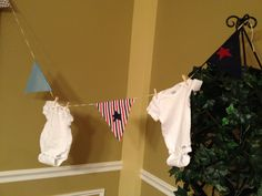 Close up of hanging onesies with nautical pennants for baby shower onesie decoration station.