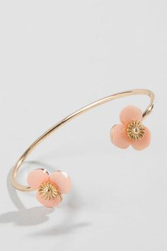 """You'll come to adore this dainty Lucille Flower Cuff Bracelet! The open gold band cuff bracelet is adorned with beautiful pale pink and gold flowers.<br /> <br /> The bangle is easy to wear and slips on and off for instant chic. Our flower cuff will compliment any look, from your best blue jeans to your more glamorous evening attire.<br /> <br /> - 2.5"""" length<br /> - Nickle & Lead Free<br /> - Imported"""
