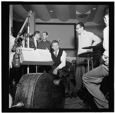 Portrait of Stan Kenton, Pete Rugolo, and Harry Forbes, Capitol studio. Caption from Down Beat: First Capitol recording session of the Stan Kenton band in the new eastern studios is pictured above by staff lensman Bill Gottlieb. Below is the maestro, looking rather woozy, talking to Pete Rugolo, arranger, with Harry Forbes in the background.