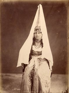 Tantour - Palestinian Head Piece - 19th-20th century. This tall, cone shaped women's head-dress is known as a Tantour or Shihabeeyen. It is made of metal with a raised pattern and painted in gold. It was worn by married women, up to the late 19th century, and would have been decorated with coins and pieces of gold.