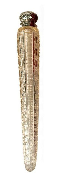 A Victorian crystal eau-De-toilette bottle with silver cover | A Victorian crystal eau-De-toilette bottle with silver cover, the bottle's long tapering baton shaped body with cut and fluted design, the hinged lid hallmarked Birmingham 1892 by Colen Hewer, Cheshire.