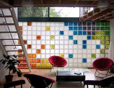 stunning house design with colorful glass block wall decor and red chair beside stairs