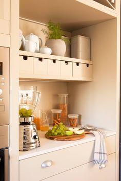 Zona de desayuno con pequeños electrodomésticos, botes de cocina, estante para juego de café y té, y cajones pequeños