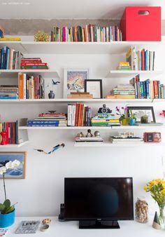 Prateleiras brancas dão leveza para o ambiente e comportam tv, livros e objetos.