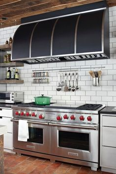 Amazing kitchen features wood plank ceiling over black barrel range hood over Wolf Range paired with wall-mounted spice rack and utensils holder mounted on white subway tiled backsplash with dark grout flanked by stacked chunky wood floating shelves over brick floor.