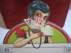 Gorgeous art deco 1920s die cut place card pretty flapper girl in holding fan with red rose decoration on her dress unused