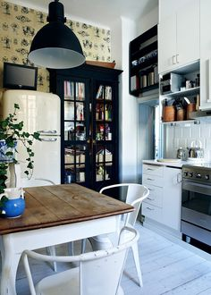 love the touch of black: storage over door, tv and pendant light over table. very cool.