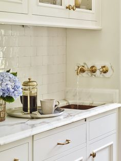 Love the wall-mounted brass faucet in this butler's pantry/bar area