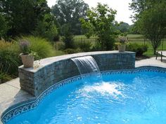 swimming pool with waterfall spout feature..nice tile on inside of pool