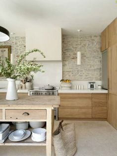 Une cuisine en bois avec un îlot et mur en pierre