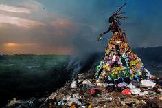 """Wie eine Dämonin steigt die Figur aus dem Müll über der noch intakten Natur. """"The Prophecy"""" von Fabrice Monteiro entstand auf einer der Mülldeponien im Senegal – ebenso das von dem Kostümdesigner Doulsy (Jah Gal) gestaltete Kleid. © Fabrice Monteiro/LagosPhoto"""