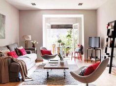 Un salón sencillo y ligero al poner un sólo sofá y dos butacas, todo de Ikea. La mesa de centro, de El Chinero,  así como la de la televisión, de Amapola, disponen de grandes ruedas. Sobre el sofá, un cuadro con un paisaje en perspectiva aumenta la profundidad visual...  de la zona de estar.