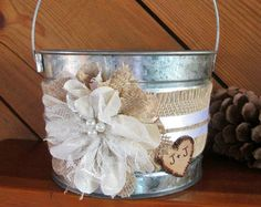 How sweet it will be to see your flower girl walk down the aisle with this unique, rustic bucket. A burlap and lace ribbon wraps around the galvanized bucket. The main feature is a handmade burlap, cotton, and lace flower. A personalized wooden heart makes it your own. This bucket measures approximately 7 round, 4 1/2 deep x 8 1/2 tall at the handle. A perfect size for your flower girl.  When the wedding is over, keep the memory of your special day by adding this rustic bucket to your home…