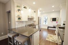 Love this kitchen! Carrera marble subway tile backsplash, white cabinets, gray countertops, dark hardwood floor, gray barstools modern yet traditional feel
