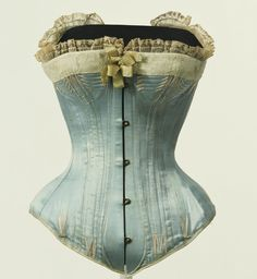 """Corset  1870-1880  Blue Silk Satin, Steel Busk, Bone  This corset is a vivid reminder of the painting, """"Nana,"""" by Edouard Manet (1832–1883). The center-front busk and bones mold the curve from the waist to the abdomen, while neatly arranging the lower abdomen, as well. Women used corsets in an effort to get closer to an ideal physical form of the time; until the beginning of the 20th century, their waists were tightened by the corset. With the development of modern technology, people a"""