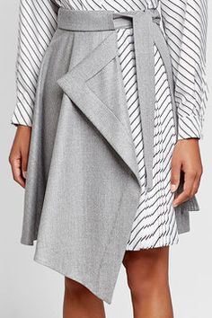 Asymmetric Skirt with Pleated Insert  | Combining pale grey wool with a panel of striped pleats, this modern but modest skirt from Carven is a chic statement. The asymmetric hemline is universally flattering and will up the attitude of any look.