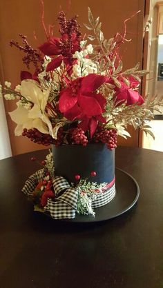 Snowman hat centerpiece! Using a coffee can, $Store plastic dinner plate, spray paint with flat black, attach pieces and decorate! You can also fill the hat with goodies instead of flowers and give as a gift! It can be used later as a centerpiece using the black coffee lid!