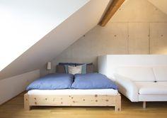 Modernes Zirbenbett im Dachgeschoss mit Sichtbeton. Gefertigt in unserer Tischlerei