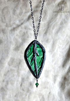 Tracery Leaf ~ A unique necklace inspired by Nature and Architectural Detail.    Textured waves of deep green Stained Glass glows within a highly detailed leaf frame.