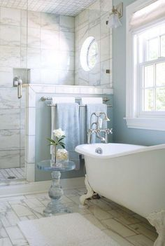 Classic and traditional blue and white bathroom with floor to ceiling carrara marble tiles in the shower, light blue wall paint, white floor tiles, glass pedestal side table, chrome silver hardware and faucet fixtures and freestanding clawfoot bathtub.