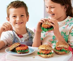 Two kids eating cheesy bean burgers, sitting in buns with lettuce