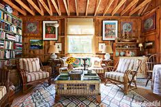 The adjacent barn, with its deliberately eclectic furnishings, invites casual entertaining. A fishtrap coffee table centers the set of 1940s Heywood Wakefield rattan in Rose Tarlow Melrose House's Wellington Stripe. An antique Moroccan rug rests atop Stark's Natura rug. Local potter Will Heacock made the lamp bases.   - HouseBeautiful.com