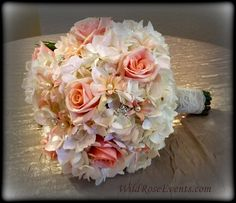 a pretty little nosegay of roses, hydrangea and hyacinth with pearl and rhinestone accents. wrapped with burlap and lace.  #WildRoseEvents #weddingFlowers #briddalbouquet #peach #pink #bling #nosegay