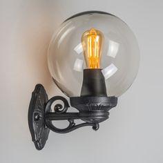 Aplique BASSO negro - Preciosa lámpara con detalles ornamentales en plástico. Esta lámpara se completa con una esfera transparente, a través de la cual se ve la bombilla. Los materiales son de alta calidad y resistentes a la intemperie y a los impactos. La fuente de luz es de casquillo E27 y funciona con varias tipos de luz (halógena, bajo consumo y LED).