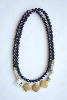 This Designs by s.e.K long navy goldstone necklace features pyrite, grey marble, brown marble, and white marble stones with an asymmetrical style and an antique brass button clasp. This necklace can be worn long or doubled for a statement look.