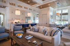 """Architect Paul Geary included transom windows in the open living room/kitchen. """"The windows convey natural light and also add separation between kitchen and family room,"""" says interior designer Courtney Dickey. """"They also give a sense of scale between the two rooms."""""""