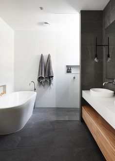 Black, timber and white accents blend throughout this bathroom design and home to create continuity throughout. ​ Designer: Austin Design Associates​ Photography: Armelle Habib​ Benchtop: Caesarstone®…More Bathroom Renos, Laundry In Bathroom, Bathroom Layout, White Bathroom, Bathroom Renovations, Modern Bathroom, Small Bathroom, Home Remodeling, Bench In Bathroom