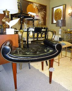 Fabulous neoclassical style bench in embossed and tufted black leather with mahogany legs ending in brass caps.