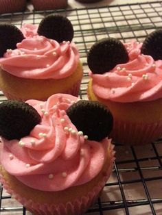 Minnie Mouse cupcakes decorated with pink buttercream icing, topped with mini Oreos, and sprinkled white edible pearls.