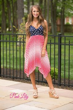 We love this adorable dress - it's perfect for staying cool and comfortable at your Fourth of July cookout! Featuring a deep v-neck, a low-cut back, spaghetti straps, and soft fabric, you'll want to wear this all day long! The pattern features diagonal red and white stripes on the skirt and navy and white polka dots on the bodice.
