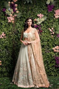 A subtle green lehenga with embroidery done in contrasting thread ,zari ,glass pipes and sequence.The dusty pink tulle dupatta has delicate pita embroidery all around and motifs scatter inside.The lehenga is finished with shimmer sequence edge.