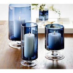 We've added the allure of deep blue to our popular London glass hurricane, a Crate and Barrel classic. Handcrafted large glass hurricane is a modern classic look with a straight-sided silhouette on a short pedestal base. Blue Candle Holders, Hurricane Candle Holders, Silver Christmas Decorations, Blue Christmas, Graduation Decorations, Blue Candles, Pillar Candles, Candle Centerpieces, Crate And Barrel