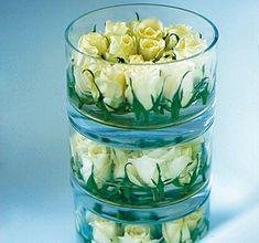Glasschale dekorieren: Blumenköpfe - etwa die von weißen Rosen - ganz kurz abschneiden. Die Köpfe müssen komplett in den Schalen verschwinden. Blütenköpfe dann ganz dicht im Kreis in die Schalen stellen, so können sie nicht umkippen. Die Schalen etwas mit Wasser füllen und übereinander stapeln.