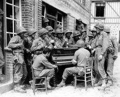 American soldiers from the2nd Armored Division partaking in a sing-along.  Barenton, France - 1944.