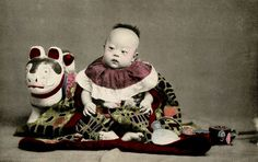 Baby with an Inu-Hariko Dog 1906    Inu-Hariko (Folk Dog Dolls) are made of Shoufu-nori paste and Kiri wood sawdust in a manner similar to papier mache and then coated with Gofun (oyster shell paste) and painted. They are traditionally thought to offer protection to new Mothers and children.