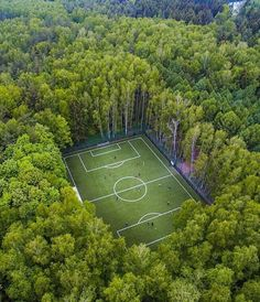 Drone shot of a soccer field in the middle of the woods in Moscow.