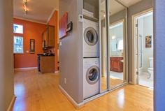 Eclectic Laundry Room with Hardwood floors, Built-in bookshelf, Whirlpool 2-cu ft Stackable Front-Load Washer, flush light